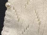 钩针做好白色毛衣将珠子钉在边缘做纽扣